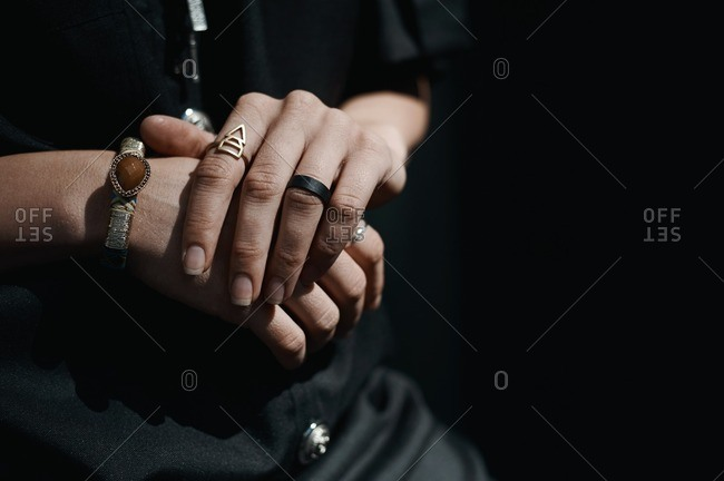 Clasped hands of a woman wearing contemporary jewelry