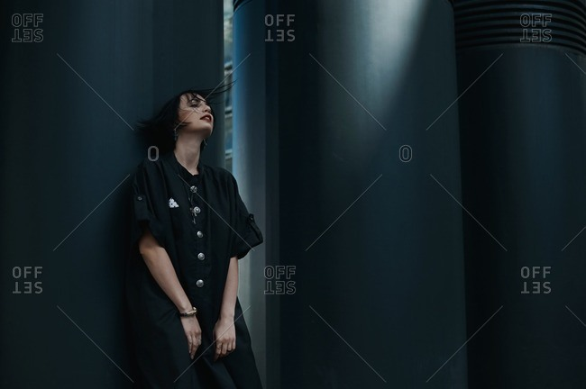 Young woman in a oversized black shift dress leaning against a wall
