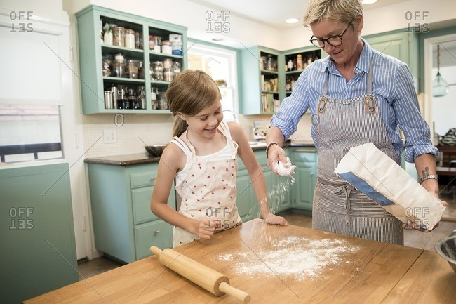 Girl helping her mom dust a kitchen countertop with flour