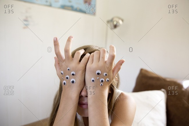 Little girl resting her face on her hands with googly eyes stuck to them