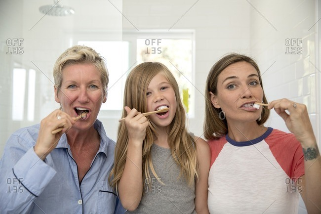 Couple and daughter brushing their teeth side by side