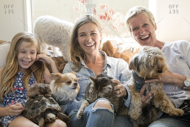 Family sitting on a couch holding all of their various pets in their laps