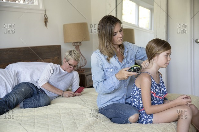 Mother brushing her daughter's hair while her wife checks her phone