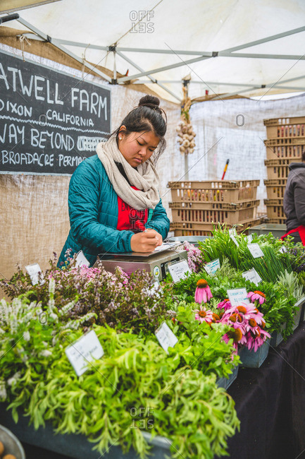 San Francisco, CA, USA - August 6, 2016: Woman selling flowers and fresh herbs at a farmers market in San Francisco