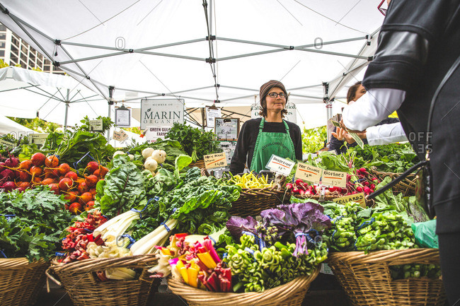 San Francisco, CA, USA - August 6, 2016: Woman selling a variety of fresh vegetables in baskets at a farmers market in San Francisco