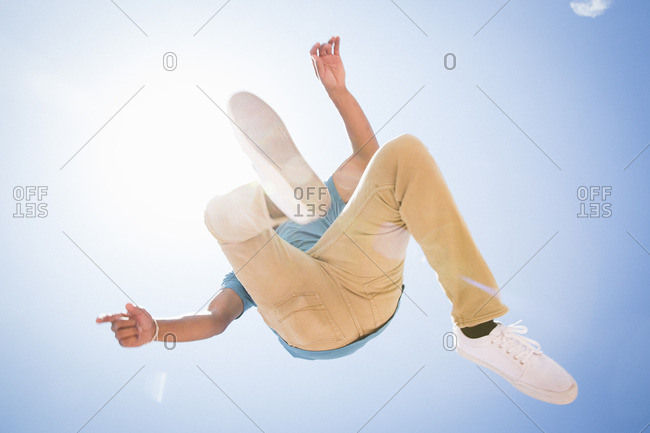 Low angle view of a young man jumping in the air