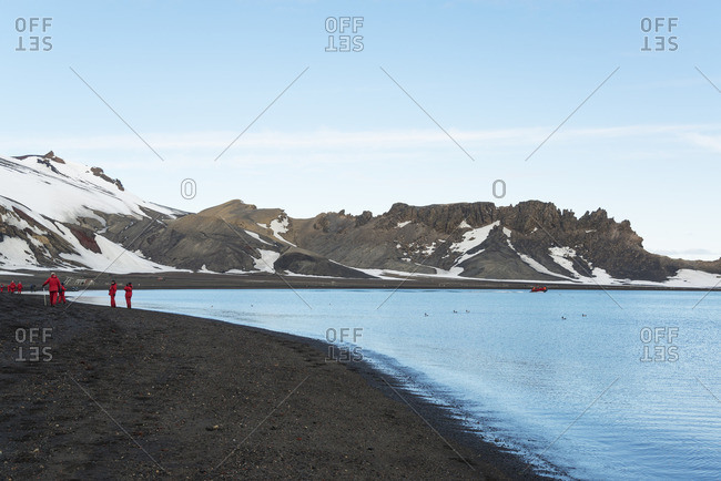 Group of people on a beach on Deception Island, snow-covered mountains in the background