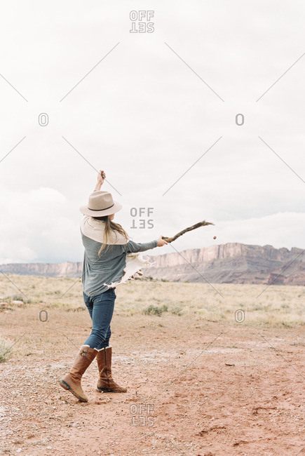 A woman with her arms raised, hitting a stone with a stick into the distance