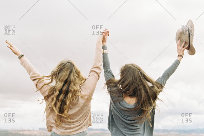 Rear view of two women standing side by side, holding hands, with their arms raised up in the air