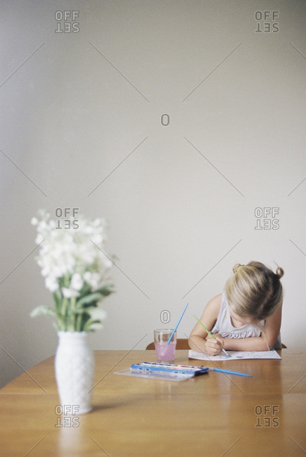 Young girl sitting at  a table, painting, a vase with white flowers
