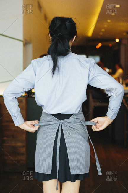 Young waitress tying her apron at a city restaurant