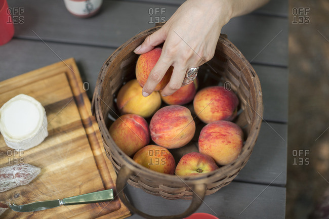 View from overhead of a picnic table with a basket of fresh peaches and a cheese board