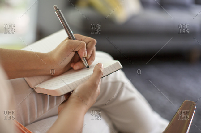 A woman seated holding an open journal and a pen