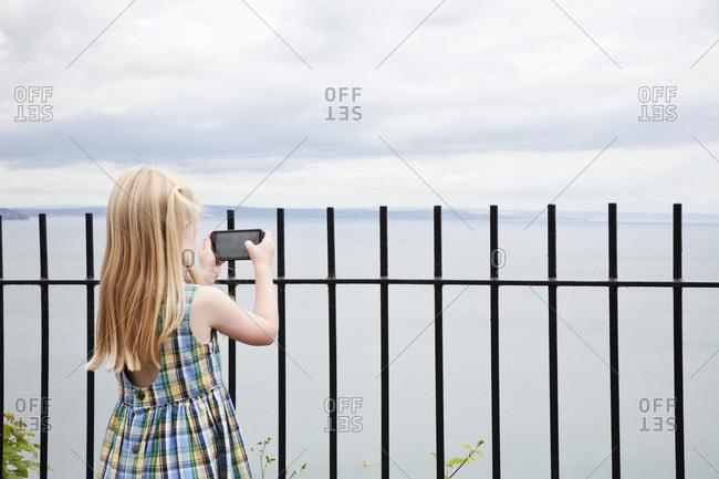 A girl in a checked sundress taking a photograph with a smart phone