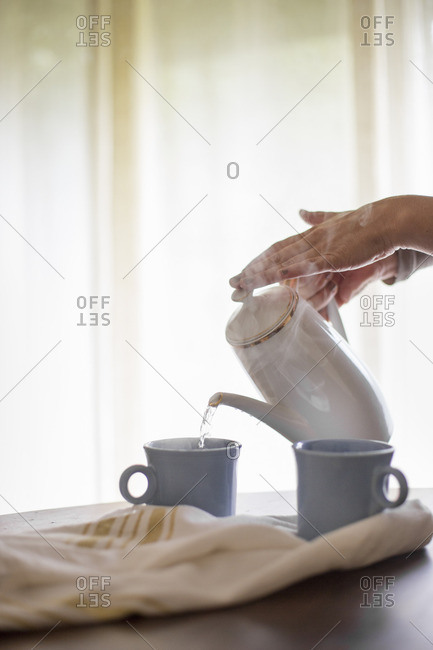 Hot water being poured from a coffee pot into a mug