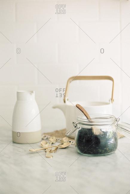 Tea pot, jug and a glass jar with black tea leaves