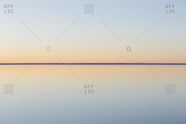 Clear line of the horizon where land meets sky, across the flooded surface of Bonneville Salt Flats Dawn light