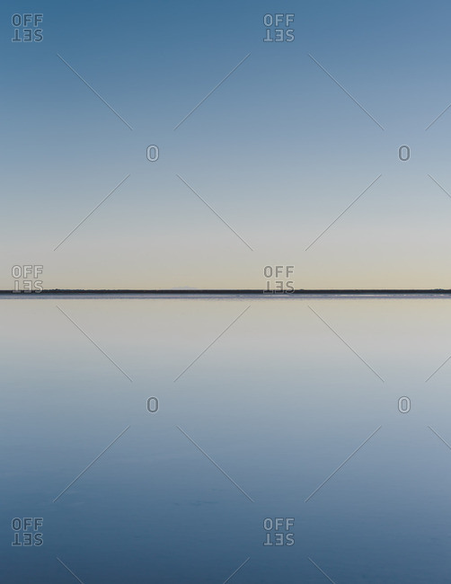 Clear line of the horizon where land meets sky, across the flooded surface of Bonneville Salt Flats Dawn light