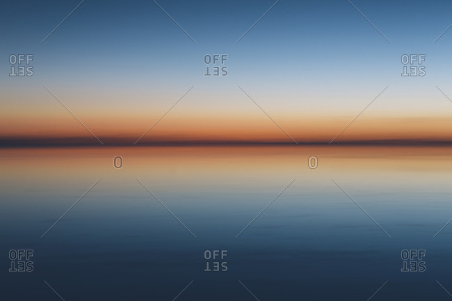 The view to the clear line of the horizon where land meets sky, across the flooded surface of Bonneville Salt Flats Dawn light