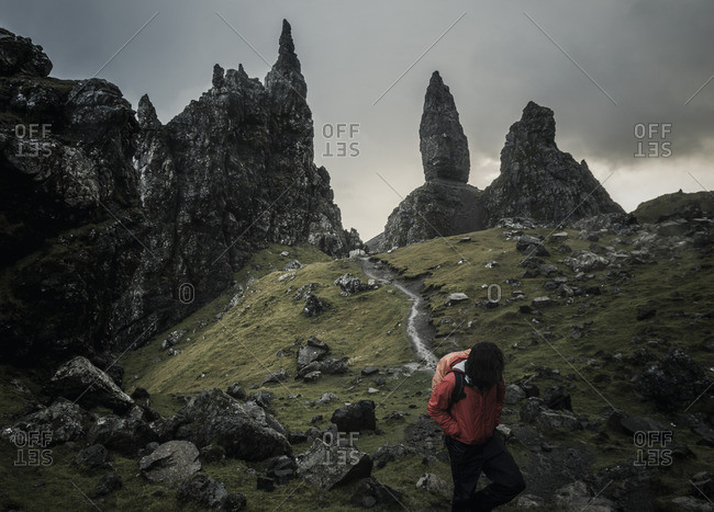 Two people with rucksacks on a narrow path rising to a dramatic landscape of rock pinnacles on the skyline towering above them
