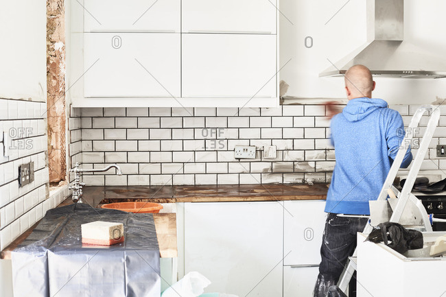 A man working in a new kitchen, a tiler applying tiles to the wall behind the cooker