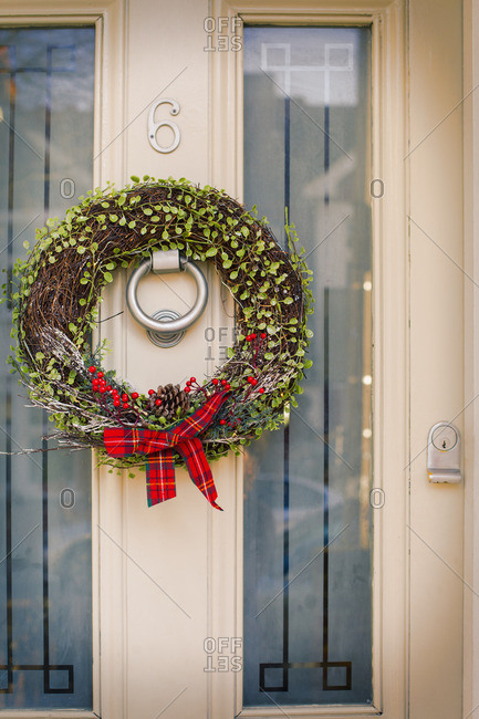 A Christmas wreath with a red bow on the front door of a house