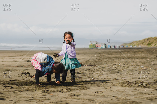 Two little girls playing in mud on a beach