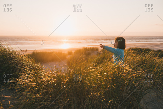 Little girl walking in tall grass on a beach at sunset