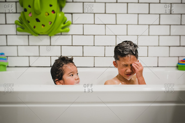 Two sisters taking a bubble bath in a white tiled tub