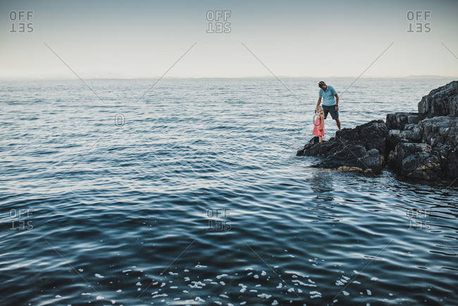 Father and daughter standing on rocks by a seaside
