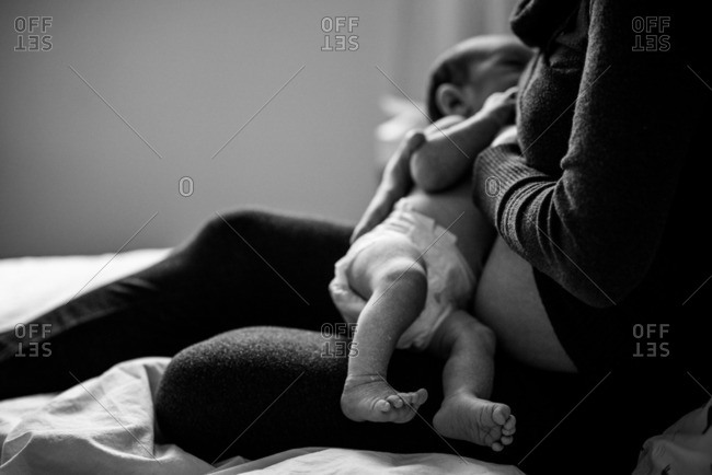 Mother sitting in bed nursing her newborn baby