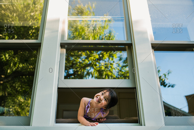 Little girl leaning out an open window smiling