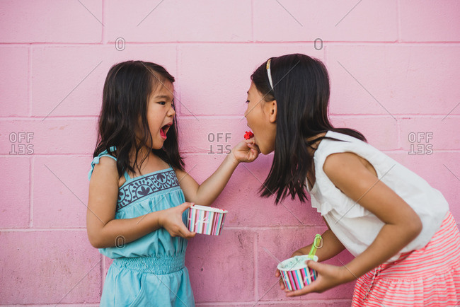 Two sisters eating frozen yogurt in front of a pink cinderblock wall