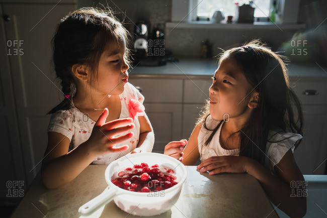 Sisters eating raspberries together from a bowl in a kitchen