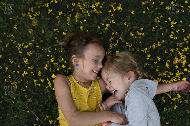 Two young sisters giggling while laying in flowers