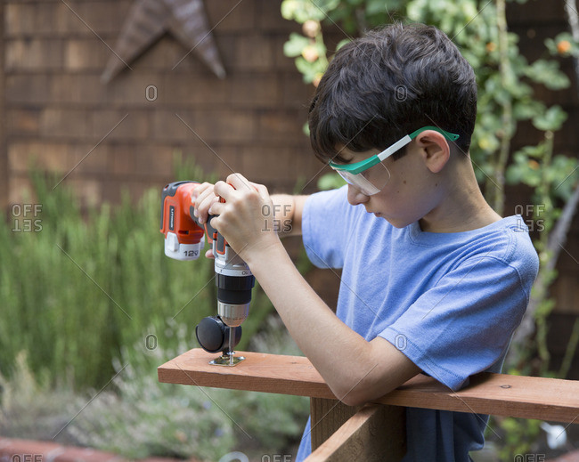 Boy using a drill for a woodworking project