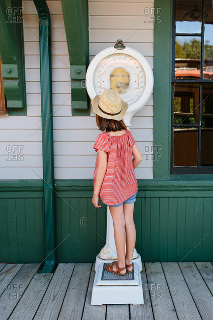 Little girl standing on an old fashioned scale