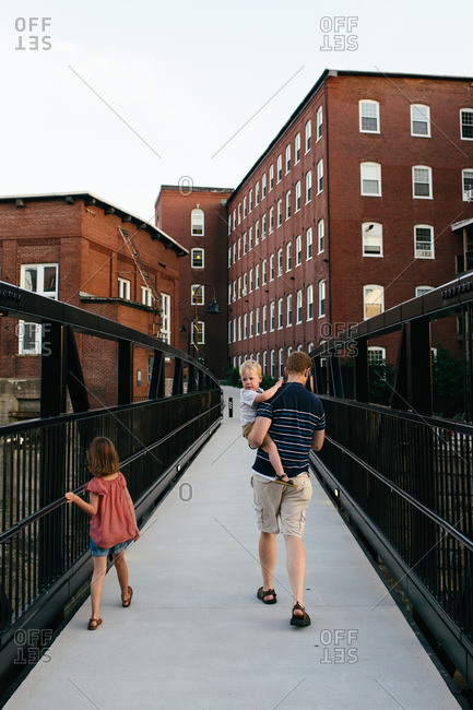 Father walking over city bridge with his two children