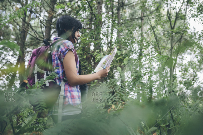 Young woman with backpack looking at hiking map in the forest