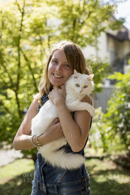 Happy woman with cat on her arms in the garden