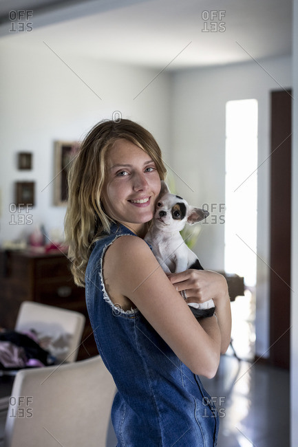 Smiling woman with dog on her arms at home