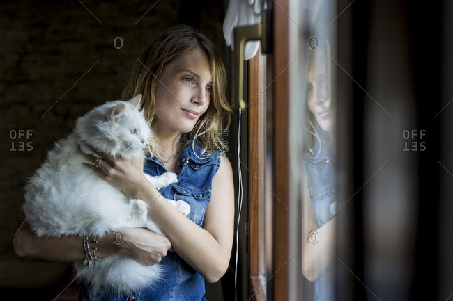 Smiling woman with cat on her arms looking through window