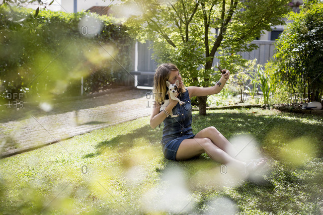 Woman taking selfie with her Chihuahua in the garden