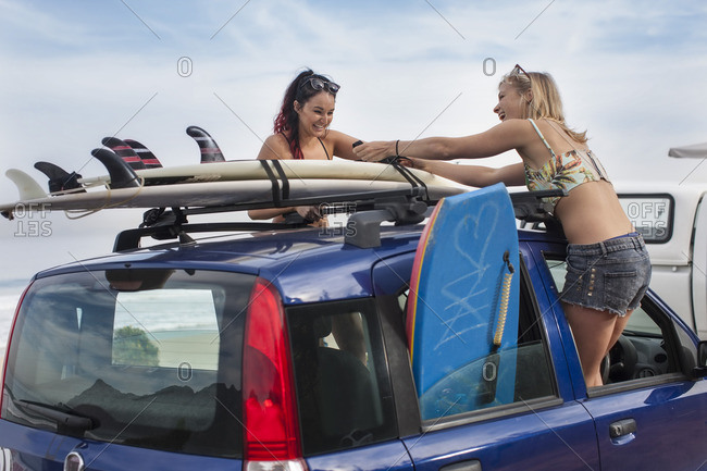 Two happy young women unwrapping surfboards on car