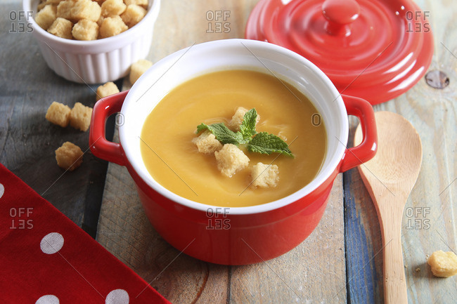 Pot of creamed pumpkin soup with bread cubes