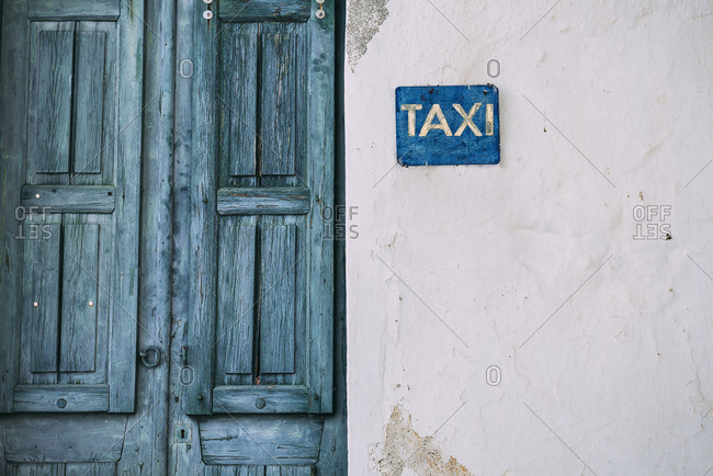 Greek, Cyclades, blue wooden door and taxi sign on the facade