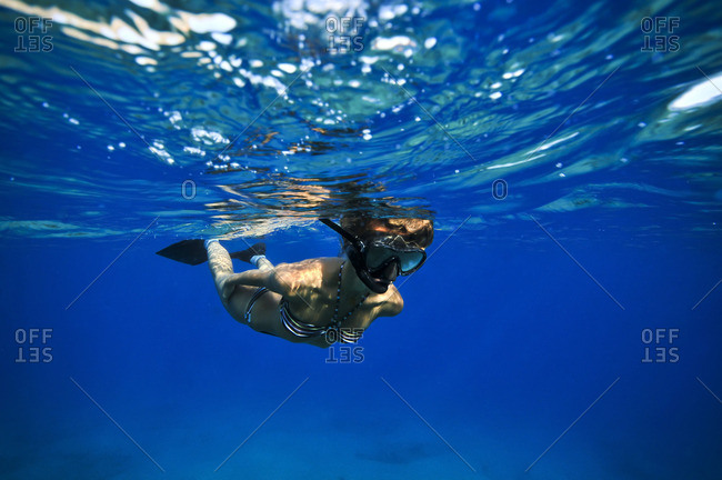 Young woman snorkeling in the ocean's blue waters