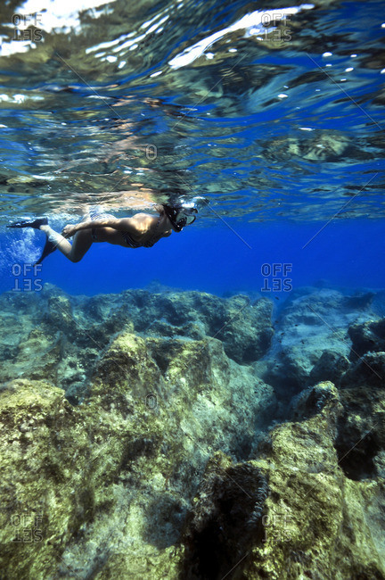 Young woman snorkeling above rocks and coral