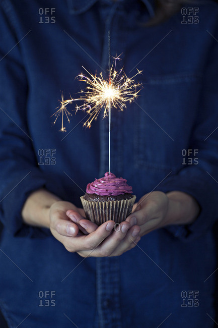 Woman holding a cupcake with a sparkler