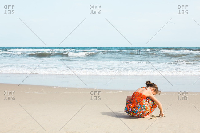 Girl writing in the sand on a beach